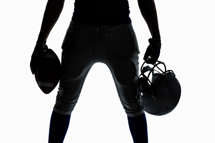 Mid section of silhouette sportsman holding ball and helmet