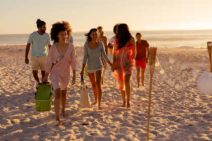 A multi-ethnic group of friends enjoying their time together on a beach on a sunny day, walking barefoot, talking to each other