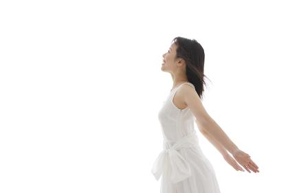 白いワンピースを着てポーズをとる若い女性