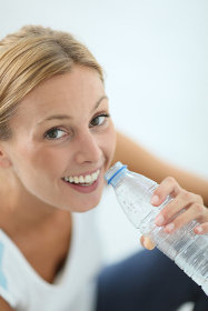 Closeup of fitness girl drinking water after exercising