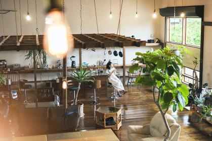 落ち着いた雰囲気の空間で、コーヒーを淹れて飲む若い女性