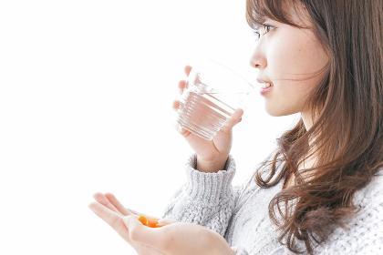 錠剤・サプリメントを飲む女性