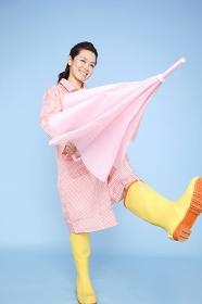 雨具を着て歩く女性