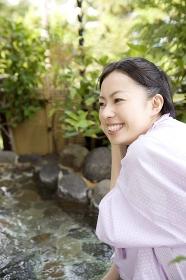 露天風呂の脇で佇む女性