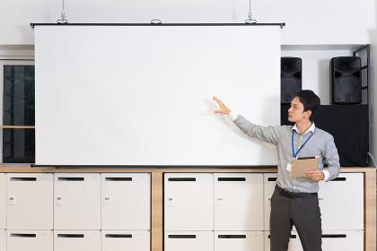 スクリーンの前でプレゼンテーションをする男性