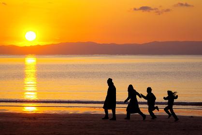 夕方の海岸を歩くシルエットの4人家族