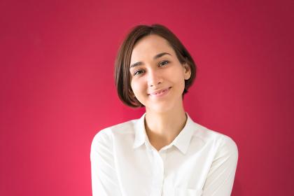 微笑む若い女性(赤い背景)