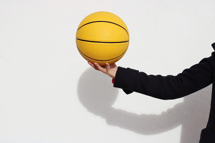 Man dressed in a black hoodie picking up a Yellow Basketball.