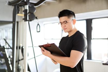 トレーニングジムでヒアリングを行うアジア人男性トレーナー