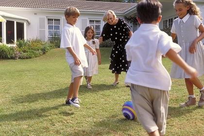 Outdoor, Frau Mitte 60 bekleidet mit schwarzen Kleid mit weissen Punkten spielt mit  ihren Enkelkindern im Garten vor dem Haus Fussball