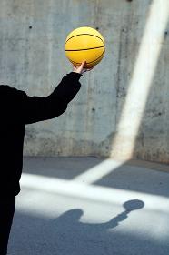 Young basketball player girl taking a yellow basketball.