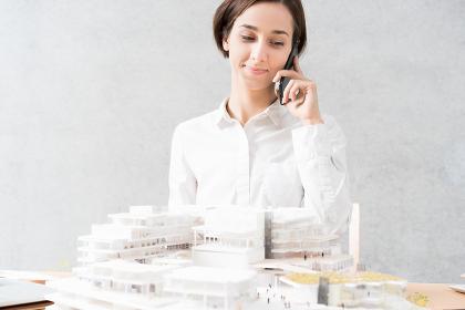 建物の模型を見ながら電話をする女性