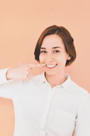 口を指差す若い女性(デンタルイメージ)