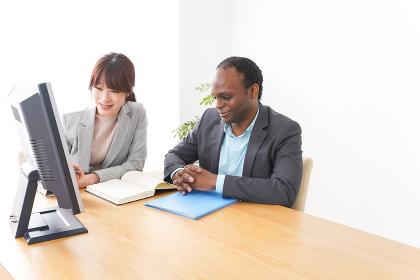オフィスでパソコンを使う2人のビジネスパーソン