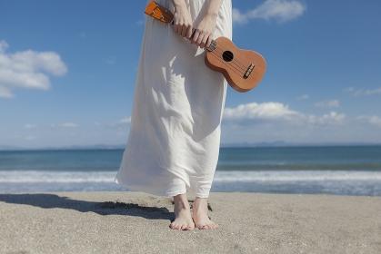 砂浜でウクレレを持って立つ日本人女性の足元