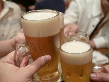 飲み会で男性と生ビールのジョッキで乾杯をする