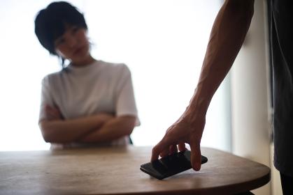 スマートフォンを手に持ち出ていく男性