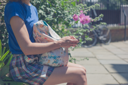 A young woman is sitting on a wall by some flowers and is using her smart phone on a sunny day
