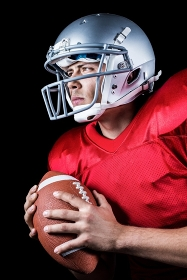 Determined American football player looking away while holding ball