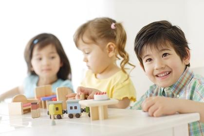 木のおもちゃで遊ぶハーフの男の子と女の子