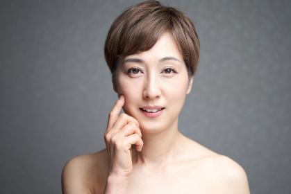 頬のハリを確かめる中年の日本人女性