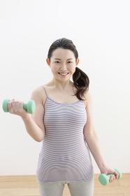 ダンベルを持ち運動する女性
