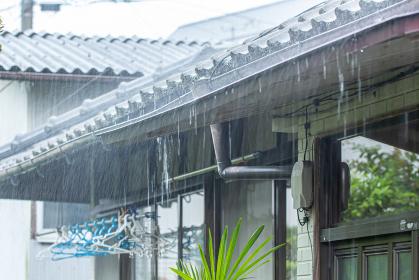 民家の瓦屋根に打ち付ける大雨