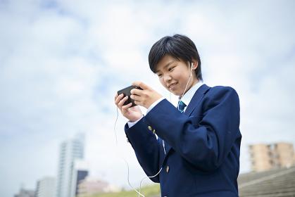 スマートフォンでゲームをする日本人男子中学生