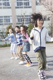 大縄跳びをする小学生4人と教師