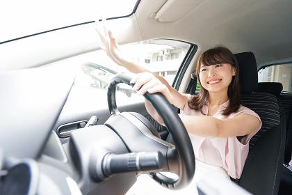 手を振る女性ドライバー