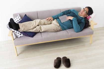 ソファでうたた寝するミドル男性
