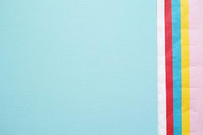 青い画用紙の右端に重なるカラフルなお花紙と広いコピースペース