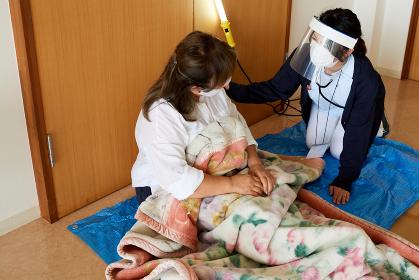 避難所イメージ 災害にあって避難所の体育館に避難してきたシニアの夫婦を救助する女性医療スタッフ
