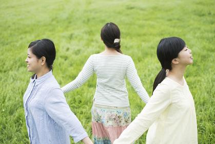 草原で手をつなぐ3人の女性
