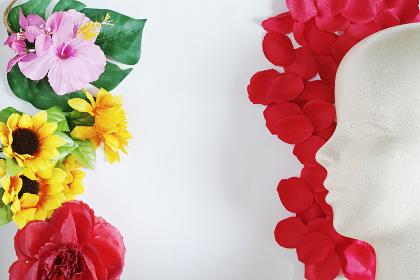 造花と赤い花びらと発泡スチロール製モデル人形の左向きの横顔