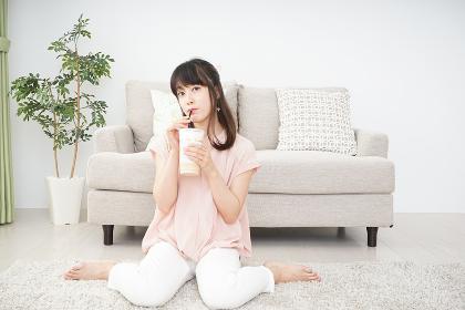 部屋でコーヒーを飲む若い女性