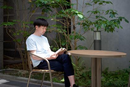 カフェで本を読む男性