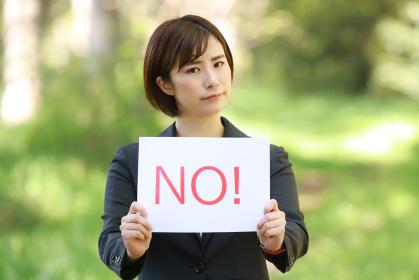 「NO!」と書かれたメッセージボードを持つ女性社員