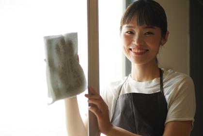 網戸の掃除をする女性