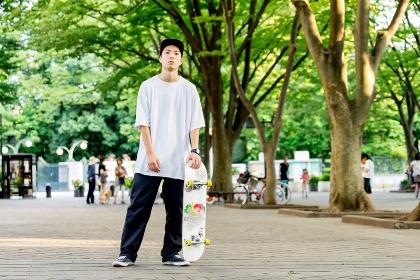 スケートボードを手に持つ男性