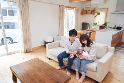 一軒家に住むパパ・ママ・赤ちゃんのアジア人ファミリー