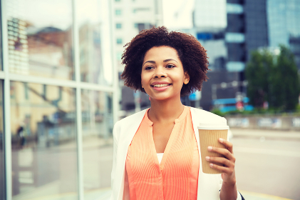 happy african businesswoman with coffee in city