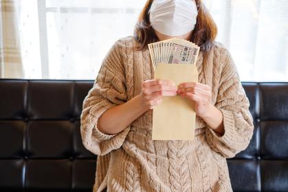 現金10万円を持つ女性 特別定額給付金 家計 へそくり