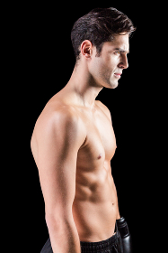 Side view of boxer standing on black background