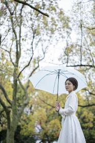 雨の公園で傘をさして佇む白いワンピースを着た若い女性