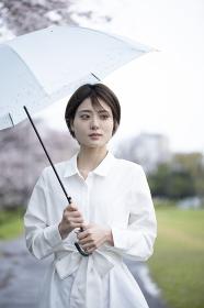 雨の中傘をさして歩く白いワンピースを着た若い女性