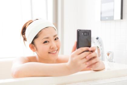 お風呂でスマホを見る女性