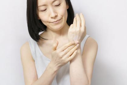 手の甲にクリームを塗る女性