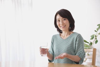 薬を飲む40代日本人女性