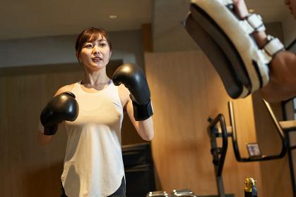 パーソナルトレーナーからキックボクシングを習うアジア人女性